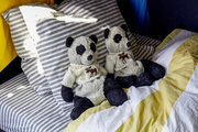 A pair of stuffed animals on a boy's bed with striped sheets