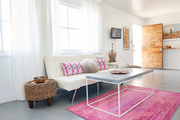 Adjacent to the kitchen is a colorful seating area with a large table and bright rug.