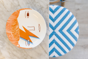 A detail of a David Bowie plate and a blue and white barstool.