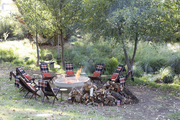 A group of chairs around a fire with plaid blankets.
