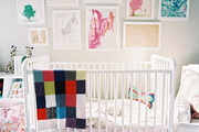 Framed children's art hung above a white Jenny Lind crib