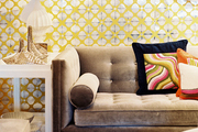 A yellow-and-silver wall pattern behind a gray sofa