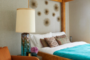 A bedroom with a bright blue comforter to match the vase sitting on the bed side table.