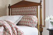 An antique child's bed upholstered in designer fabric