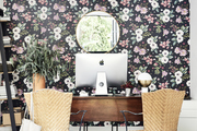 A feminine workspace with floral wallpaper.