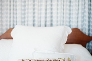 An embroidered pillow and white bedding paired with a wooden headboard