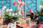 A festive table set with colorful runners and potted orchids