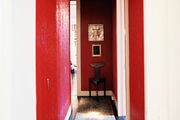 Red walls and a leopard-print carpet runner in a long hallway