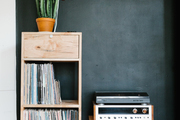 A record player and cabinet in front of a dark green wall.