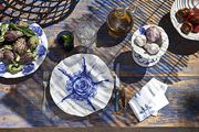 Blue and white porcelain dishes painted by artist Pepa Poch on a table made from a reclaimed door.