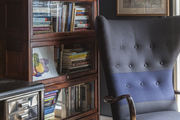 A tufted wingback chair beside a wooden bookcase