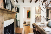 A rustic wooden mantel adorned with art in a dining space