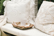 A detail of a neutral sitting area with plush pillows and a rustic tray.