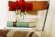 A stack of books and a vase of red roses on a chair with plaid upholstery
