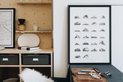 A black and white workspace with a black Eames chair and a sheepskin.