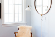Round mirror and a vintage chair with a sheepskin.
