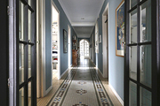 A narrow hallway with French doors and framed artwork on the walls