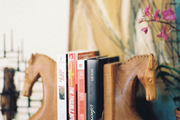 Horse-head bookends on a wooden surface