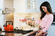 Katie Lee in a kitchen with a stainless-steel range and marble countertops