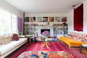An eclectic living space with a red rug and yellow sofa.