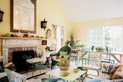 An open living-dining space filled with wicker, floral upholstery, and baskets