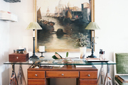 A large framed artwork above a wooden desk and a glass-topped sawhorse table
