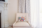 A white chair with a needlepoint pillow beside a white fireplace mantel