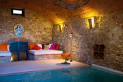 A subterranean pool and spa area with stone walls, a barrel-vaulted ceiling, and an abstract light fixture