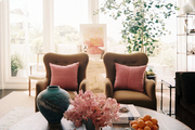 A pair of tan armchairs with pink pillows