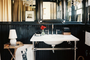 A black bathroom with mirrored panels and a pair of double-arm sconces