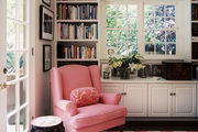 A pink wingback chair with a pink-striped rug