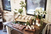 Hors d'oeuvres and flowers atop a wooden table.