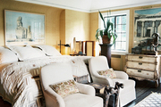 A pair of upholstered armchairs at the foot of a bed