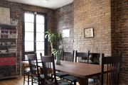 A wooden table in a brick-walled dining space
