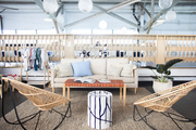 A modern boho lounge space with rattan chairs.