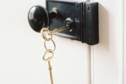 Gold keys and a black doorknob with a white door