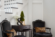 Eclectic furnishing in front of black and white staircase.
