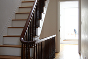 A wooden stair banister and a hallway of hardwood floors