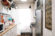 A kitchen with butcher-block countertops, white cabinetry, and stainless-steel appliances