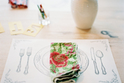 A paper place mat with a floral napkin