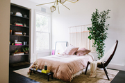 This room features a soft bed surrounded by art, a wall hanging, open shelving, and other adornments.