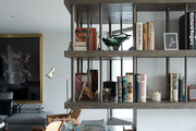 Open shelving over a concrete fireplace in the living room of London designer Tara Bernerd