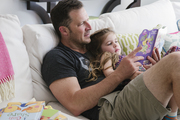 Father and daughter read storybook's on a roomy white sectional