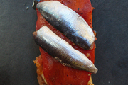 An appetizer of sardines and roasted pepper on toast