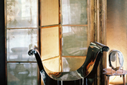 An antiqued-mirrored folding screen and a black lacquered bench