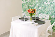 A small dining table in front of patterned leaf wallpaper.