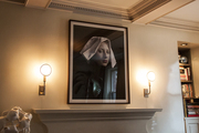An oversize portrait over a fireplace mantel