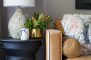 A detail of a black drum table next to a tan couch.
