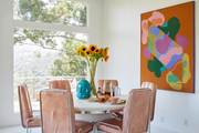 A dining room table with leather chairs and a colorful piece of art work.
