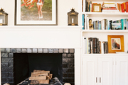 A built-in bookcase beside a white mantel decorated with art and a pair of sconces